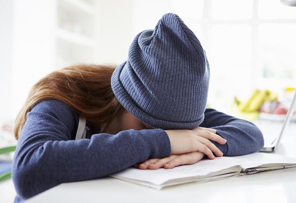 Jente sitter ved pulten og er sliten (www.colourbox.com)